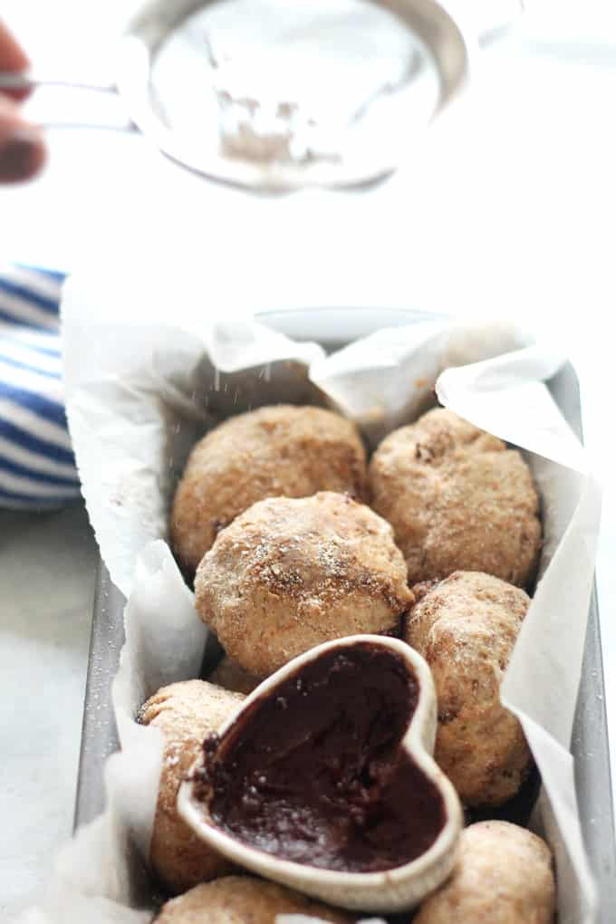 Low Sugar Chocolate Doughnuts | Raising Sugar Free Kids - delicious, light, fluffy doughnuts filled with gooey chocolate ganache. These doughnuts have all the decadent taste and texture of a fried seaside doughnut, but are baked, wholemeal, and low in sugar!